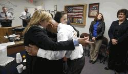 Christine Mumma, director of the North Carolina Center on Actual Innocence, left, and Cheryl Sullivan, staff attorney, hug Joseph Sledge after a special session of superior court in Whiteville, N.C. on Friday, Jan. 23, 2015. Sledge, 70, was freed from prison Friday, after a panel of judges found that he was wrongly convicted in the stabbing deaths of a mother and daughter nearly four decades ago.