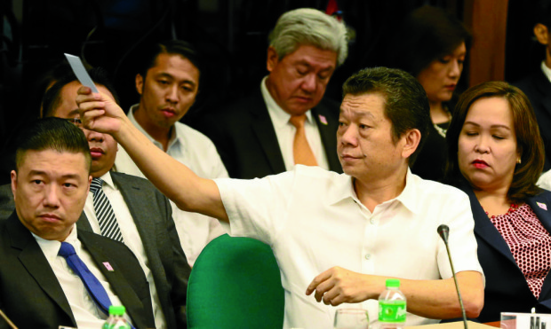 Casino junket operator Kam Sin Wong hands over a slip of paper where he had written phone numbers during the Senate Blue Ribbon committee investigation into the $81 million funds stolen from the Bangladesh Bank and deposited into bank accounts in Rizal Commercial Banking Corp.'s Jupiter branch in Makati City. INQUIRER PHOTO/LYN RILLON