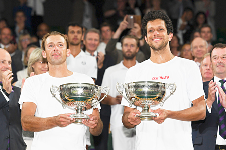 Poland's Lukasz Kubot (L) and Brazil's Marcelo Melo (R) hold up their winners' trophies during the presentation after beating Austria's Oliver Marach and Croatia's Mate Pavic during their men's doubles final match on the twelfth day of the 2017 Wimbledon Championships at the All England Lawn Tennis Club in Wimbledon, southwest London, on  July 15, 2017. photo: AFP