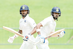 Indian cricketer Shikhar Dhawan (L) and teammate Lokesh Rahul (R) run between the wickets during the first day of the third and final Test match between Sri Lanka and India at the Pallekele International Cricket Stadium in Pallekele on Saturday. 	photo: AFP