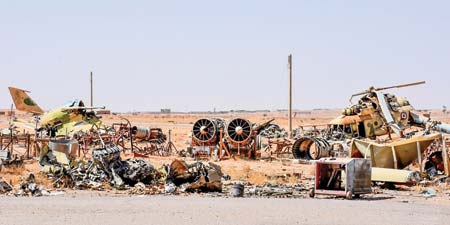 A picture shows destroyed fighter jets and a helicopter at the military airport in the eastern Syrian city of Deir Ezzor on September 12, as Syrian government forces continue to press forward with Russian air cover in the offensive against Islamic State group jihadists across the province.    Photo : AFP