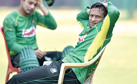 In this photograph taken on March 20, 2016, Bangladeshi cricketer Shakib-ul-Hasan (R) and a teammate take a break during the team practice session at The Chinnaswamy Stadium in Bangalore, on the eve of their World T20 cricket tournament match against Australia.    photo: AFP