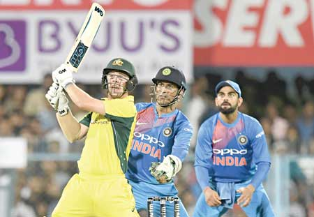 Australia's Tim Head plays a shot as India's captain Virat Kohli(R) and wicketkeeper Mahendra Singh Dhoni look on during the second T20 match of the India-Australia cricket series at the Assam Cricket Association stadium in Guwahati on Tuesday. photo: AFP