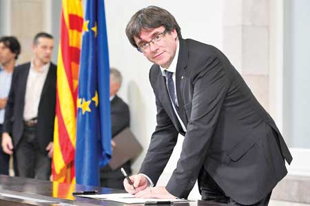 Spain's Prime Minister Mariano Rajoy gives a press conference after a crisis cabinet meeting at the Moncloa Palace on October 11 in Madrid. Right: Catalan regional government president Carles Puigdemont signs a document about the independence of Catalonia at the Catalan regional parliament in Barcelona on October 10. Photo : AFP