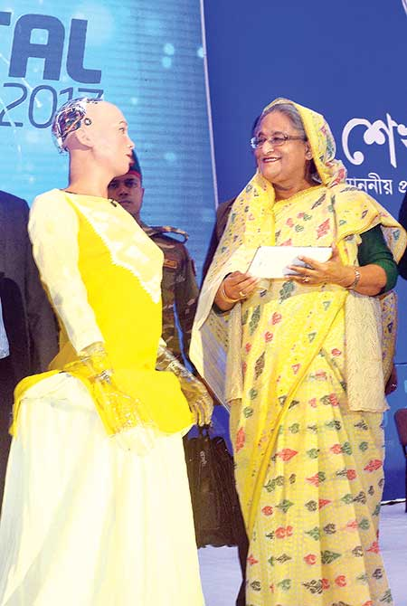 Humanoid robot Sophia and Prime Minister Sheikh Hasina sharing a moment on stage where the robot greeted her at the Digital World 2017 expo at Bangabandhu International Conference Centre on Wednesday. The two then conversed in English.    photo: pid