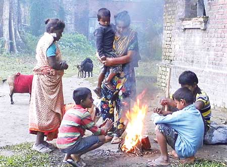 Winter has started hitting the ultra poor people in Lalmonirhat. The photo taken recently shows a poor family at Saheb Para area of the town trying to get warm by firing straw. 	photo: Observer