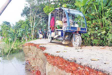 Due to deplorable condition of Kusherchar-Talappar road under No. 9 ward in Manikganj Municipality, an easy-bike is crossing the road amid risk of accident. 	photo: Observer