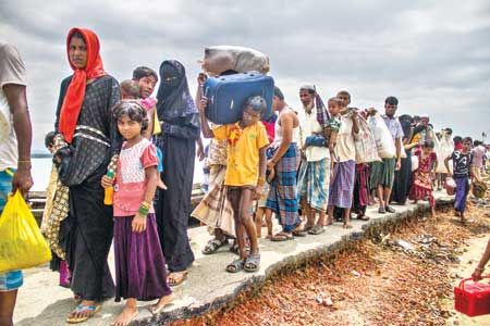 Rohingya refugees make their way to a refugee camp after crossing the Bangladesh-Myanmar border in Shahporir Dip of Cox's Bazar.     file photo