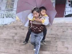 9-year old Chinese girl carries disabled older brother to school on her shoulders every day