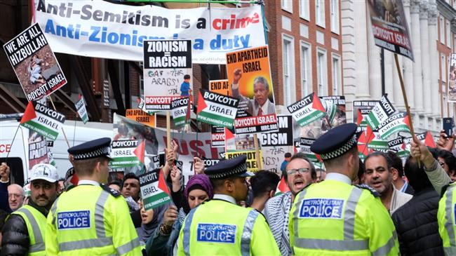 Police watch as protesters rally on Quds Day in London in 2016