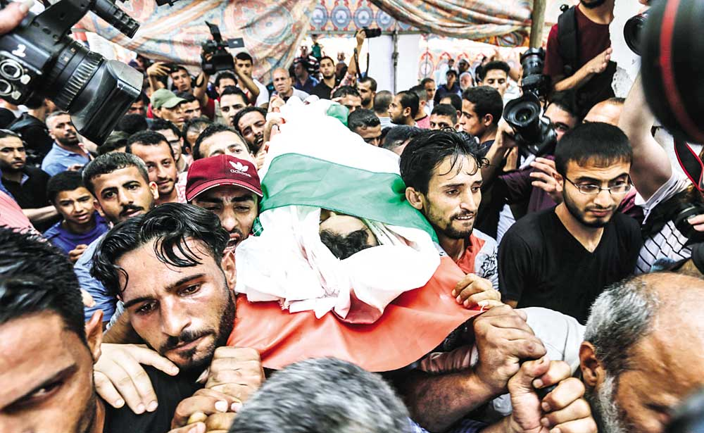 Mourners carry the body of 16-year-old Palestinian Louai Kaheel during his funeral in Gaza City on July 15 after he was killed the day before during Israeli air strikes on the Gaza Strip. Aged 15 and 16, two Palestinians were on a road west of Gaza City when an air strike struck a nearby empty building, the enclave's health ministry said. Israel unleashed a wave of strikes against Gaza on July 14, while scores of rockets were fired back across the border from the territory.photo : AFP