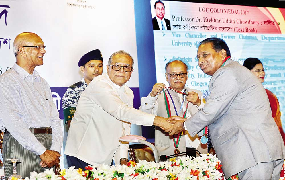 Chittagong University Vice Chancellor Professor Dr Iftekhar Uddin Chowdhury receives UGC Gold Medal Award from its Chairman Professor Dr Abdul Mannan recently.	photo : observer