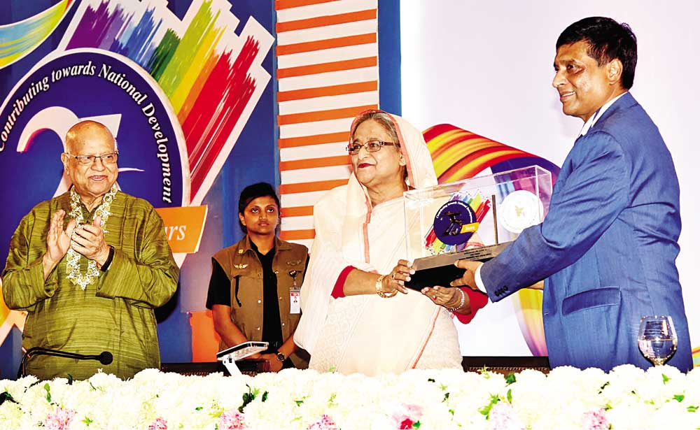 BSEC Chairman Dr M Khairul Hossain handing over a crest to Prime Minister Sheikh Hasina at a programme marking the celebration of the Silver Jubilee of Bangladesh Securities and Exchange Commission (BSEC) at Bangabandhu International Conference Centre in the capital on Wednesday.	photo : pid
