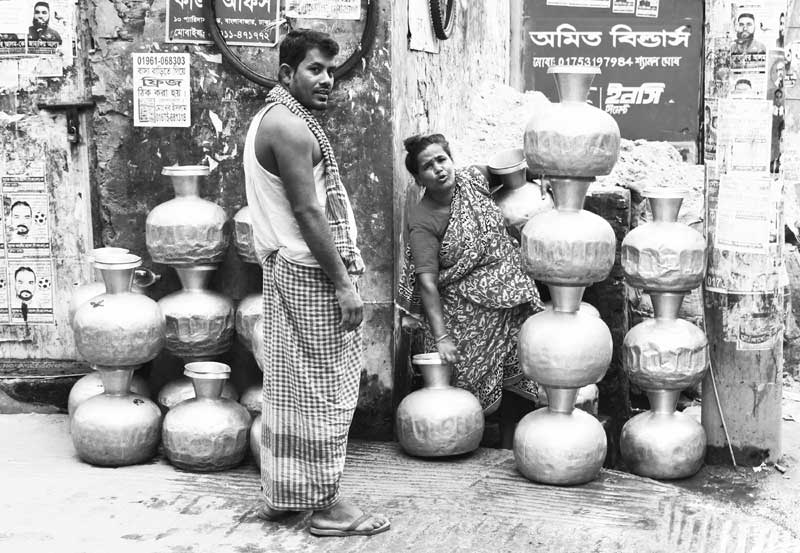 Locals waiting with jars in front of a WASA water pump