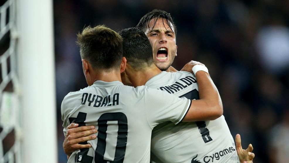 Juventus's forward Cristiano Ronaldo, right, celebrates with his teammates Paulo Dybala, left, and Rodrigo Bentancur after scoring during a Serie A soccer match between Udinese and Juventus, at the Dacia Arena stadium in Udine, Italy, Saturday, Oct.6, 2018. (Stefano Lancia/Ansa via AP)
