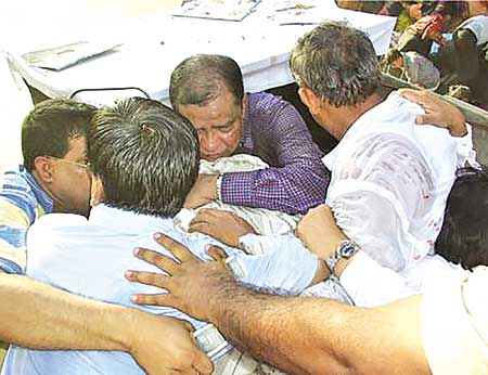Awami League leaders form human shield to protect Sheikh Hasina during the grenade attack on an AL rally in the city on August 21, 2004.  file photo