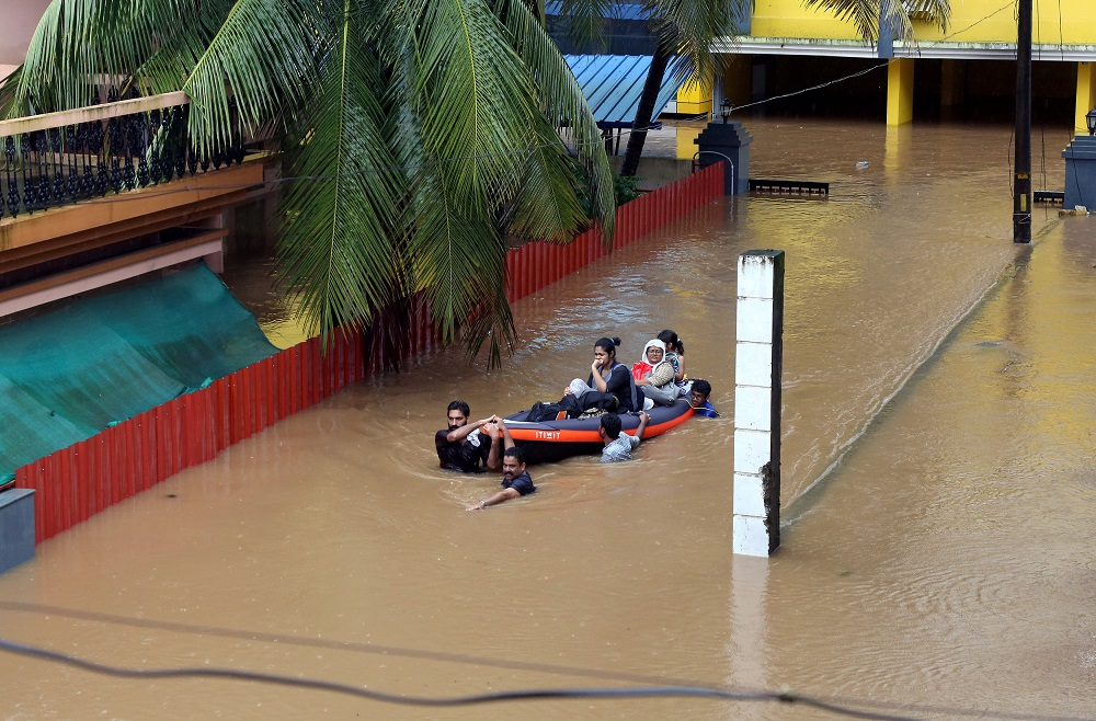 Rescue workers evacuate people from flooded areas after the opening of Idamalayr, Cheruthoni and Mullaperiyar dam gates following heavy rains, on the outskirts of Kochi, India, August 16, 2018. — Reuters pic