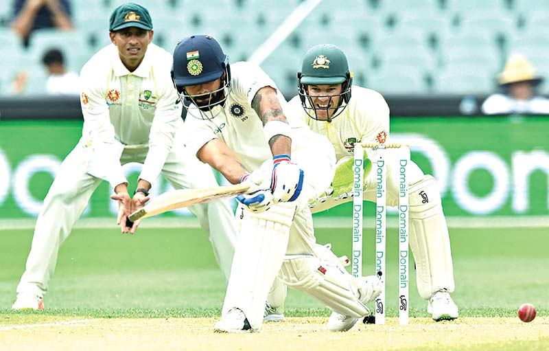 India's captain Virat Kohli (C) hits a ball watched by Australia's cricket captain Tim Paine (R) during day three of the first Test cricket match at the Adelaide Oval on Saturday.	photo: AFP