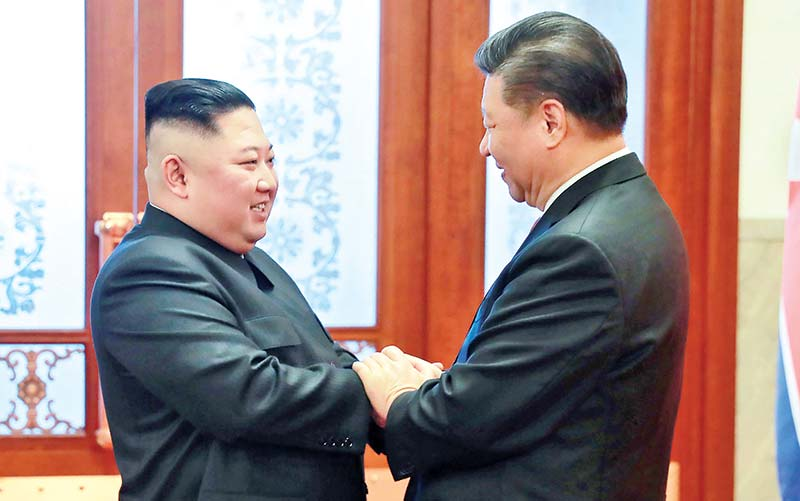 This January 8 picture released by North Korea's official Korean Central News Agency (KCNA) on January 10 shows North Korea's leader Kim Jong Un (L) being greeted by China's President Xi Jinping (R) during a welcome ceremony at the Great Hall of the People in Beijing.	photo : AFP