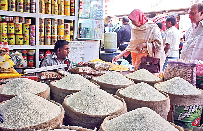 Consumers at a shop of a kitchen market at Sepoybagh in the capital on Friday. Wholesale prices of all varieties of rice have gone up by at least Tk 2 per kg, making the staple costlier in the retail market in the beginning of the New Year.	photo: Observer