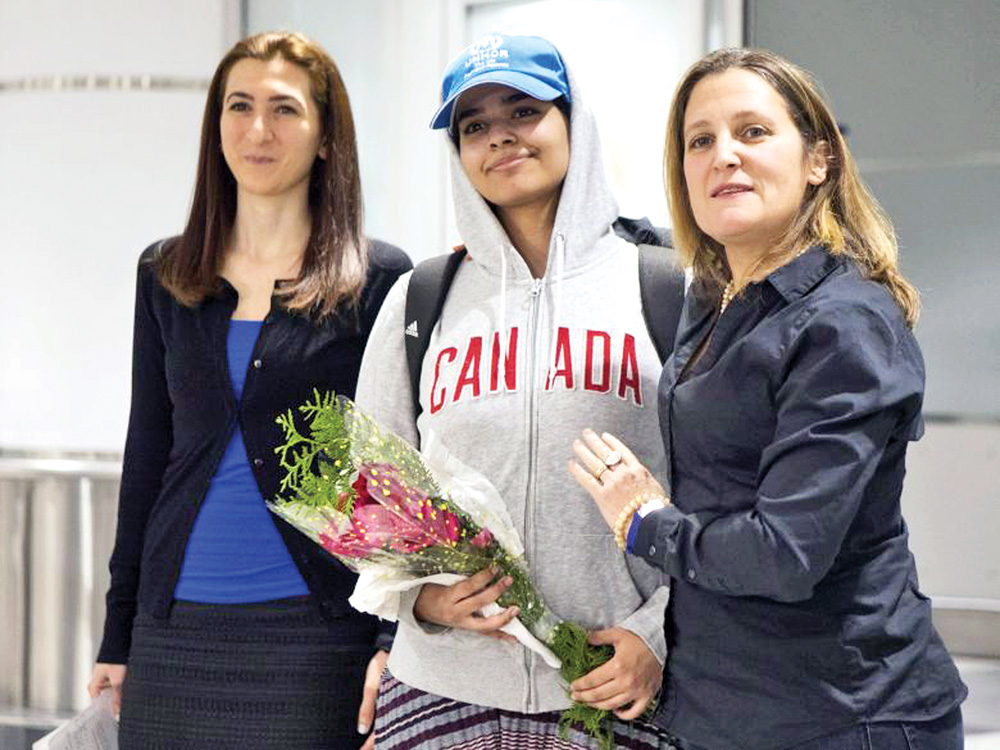 Saudi teenager Rahaf Mohammed Alqunun, centre, stands with Canadian Minister of Foreign Affairs Chrystia Freeland, right, as she arrives at Toronto Pearson International Airport.photo : the canadian press