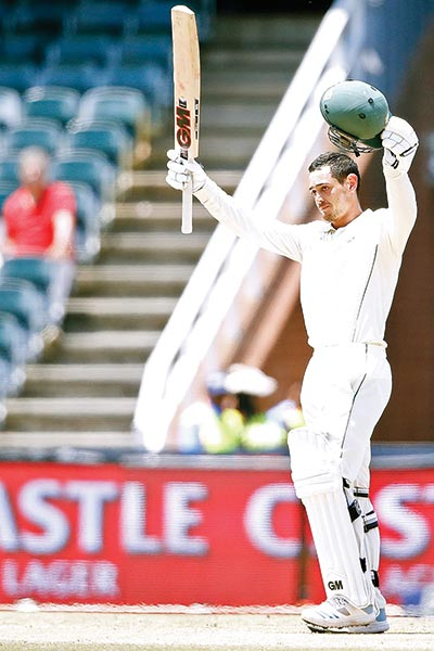 South African batsman Quinton de Kock raises his bat and helmet as he celebrates his century (100 runs) during the third day of the third Cricket Test match between South Africa and Pakistan at Wanderers cricket stadium in Johannesburg, South Africa on Sunday.photo: AFP