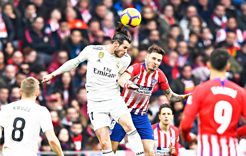 Real Madrid's Welsh forward Gareth Bale (C-L) heads the ball with Atletico Madrid's Spanish midfielder Saul Niguez (C-R) during the Spanish league football match between Club Atletico de Madrid and Real Madrid CF at the Wanda Metropolitano stadium in Madrid on February 9, 2019.	photo: AFP