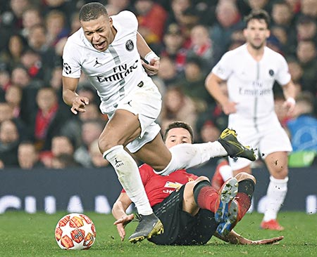 Manchester United's Spanish midfielder Ander Herrera (C) fouls Paris Saint-Germain's French striker Kylian Mbappe (L) during the first leg of the UEFA Champions League round of 16 football match between Manchester United and Paris Saint-Germain (PSG) at Old Trafford in Manchester, north-west England on Tuesday. 	photo: AFP