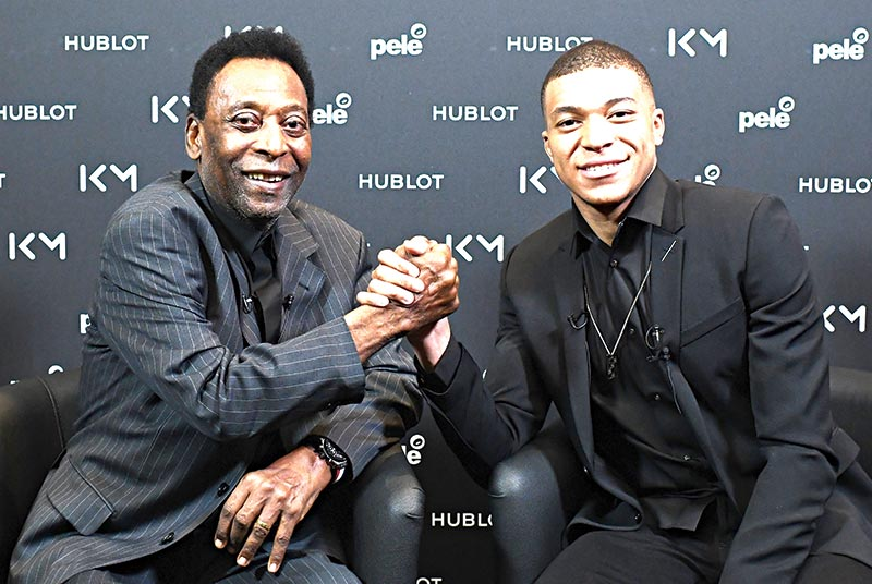 Paris Saint-Germain (PSG) and France national football team forward Kylian Mbappe (R) and Brazilian football legend Pele shake hands  during their meeting at the Hotel Lutetia in Paris on April 2, 2019.