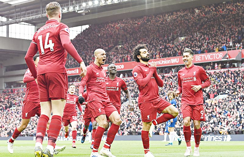 Liverpool's Egyptian midfielder Mohamed Salah (C) celebrates with teammates after scoring their second goal during the English Premier League football match between Liverpool and Chelsea at Anfield in Liverpool, north west England on April 14, 2019.photo: AFP