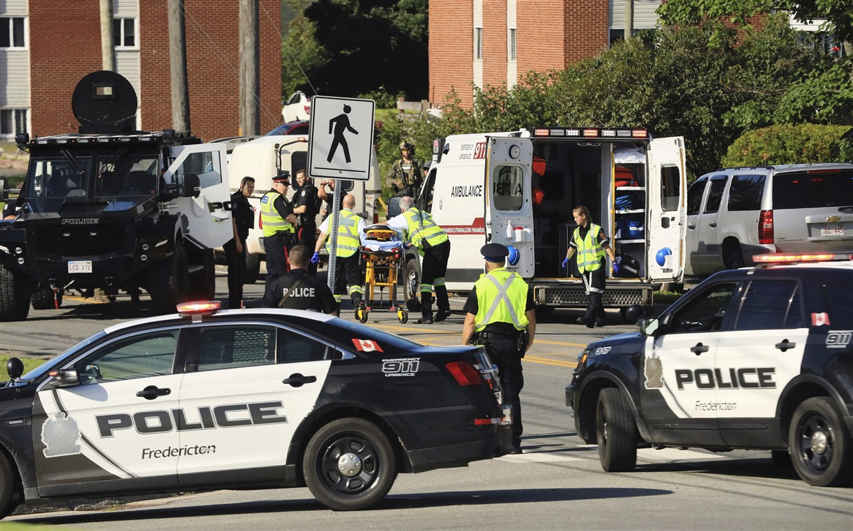 Police officers and paramedics survey the area of a shooting in Fredericton, New Brunswick, Canada on Aug. 10, 2018.Keith Minchin / The Canadian Press via AP
