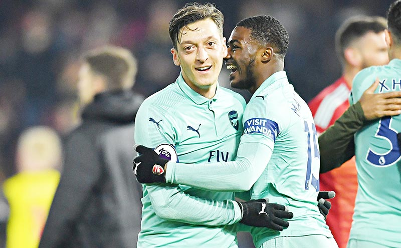 Arsenal's German midfielder Mesut Ozil (L) celebrates with Arsenal's English midfielder Ainsley Maitland-Niles on the pitch after the English Premier League football match between Watford and Arsenal at Vicarage Road Stadium in Watford, north of London on April 15, 2019. Arsenal won the game 1-0.photo: AFP