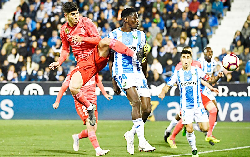Real Madrid's Spanish midfielder Marco Asensio (R) challenges Leganes' Nigerian defender Kenneth Omeruo during the Spanish league football match between Club Deportivo Leganes SAD and Real Madrid CF at the Estadio Municipal Butarque in Leganes on April 15, 2019.	photo: AFP
