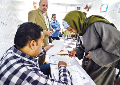 An elderly Egyptian man signs off while voting at a polling station in a referendum on constitutional amendments, at a school in the Haram district in the capital Cairo's western twin city of Giza, on the first day of a three-day poll, on April 20.	photo : AFP