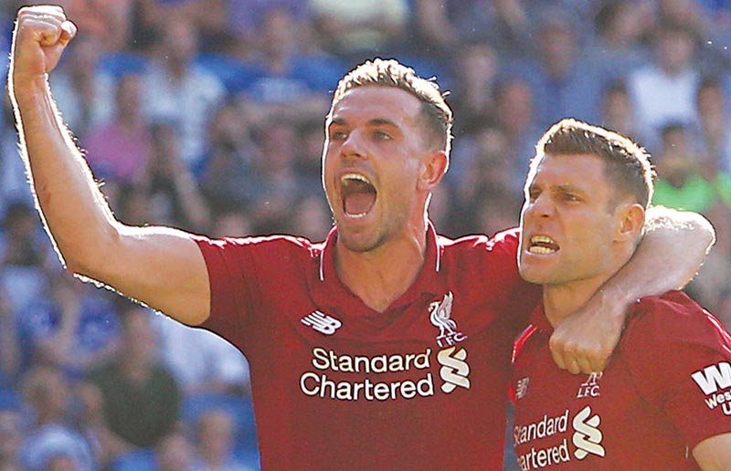 Liverpool's English midfielder James Milner (R) celebrates scoring their second goal from the penalty spot with Liverpool's English midfielder Jordan Henderson (L) during the English Premier League football match between between Cardiff City and Liverpool at Cardiff City Stadium in Cardiff, south Wales on April 21, 2019.	photo: AFP