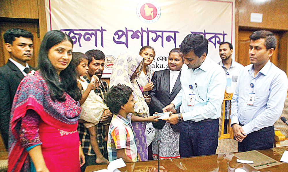 Deputy Commissioner of Dhaka Abu Saleh Md Ferdous Khan handing over a cheque of Tk 10,000 to a destitute family at the DC Office in presence of Social Ministry officials, lawyers and journalists in the city on Wednesday after a  photograph of a sleeping child tethered to her mother with a rope was published in The Daily Observer on May 21 which drew the attention of the authorities to mitigate their plight.Photo : Jibon Amir