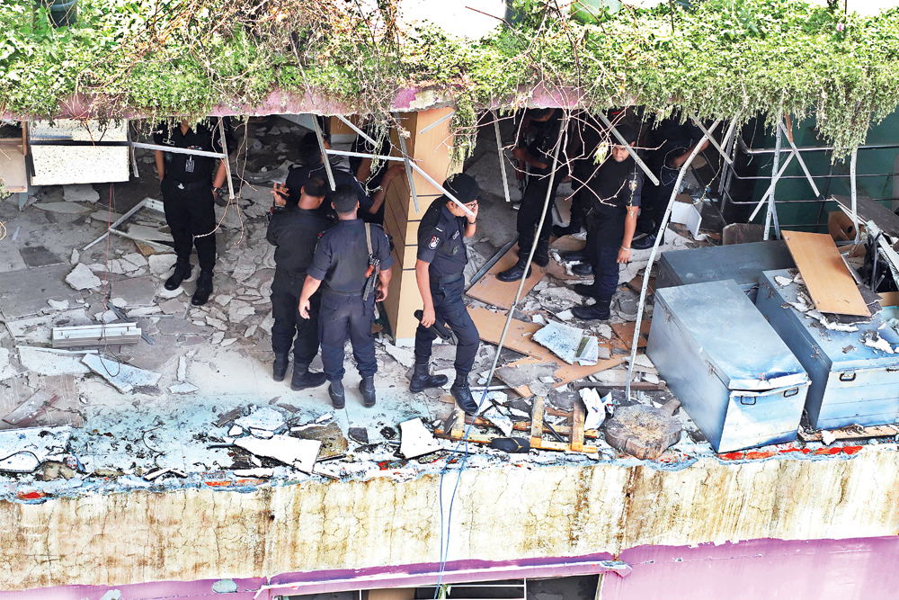 RAB members inspecting a building at Shanir Akhra in the capital on Monday after a person was killed in a wall collapse triggered by an explosion in the building.photo: Observer