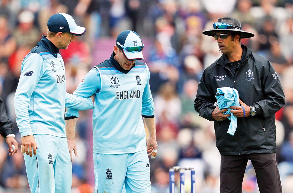 England's captain Eoin Morgan (C) is assisted by teammate Joe Root (L) as he walks off the fields with an injury during the 2019 Cricket World Cup group stage match between England and West Indies at the Rose Bowl in Southampton, southern England, on  June 14, 2019.	Photo: AFP