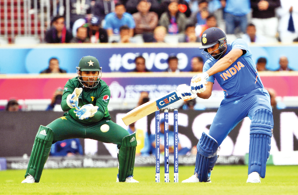 India's Rohit Sharma (R) plays a shot as Pakistan's captain Sarfaraz Ahmed looks on  during the 2019 Cricket World Cup group stage match between India and Pakistan at Old Trafford in Manchester, northwest England, on June 16.Photo: AFP