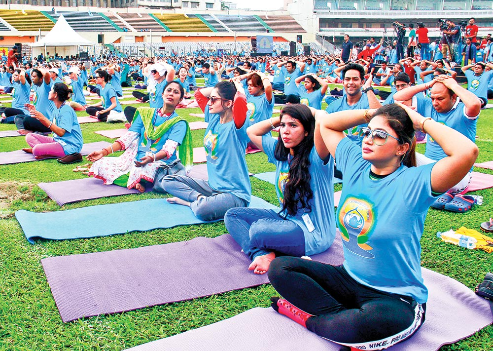 Women along with men join a yoga session at Bangabandhu National Stadium in the capital on Friday. Indian High Commission organized the session to celebrate the International Day of Yoga.	photo : Observer