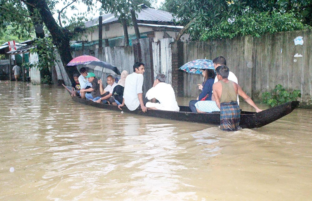Some people going to their destination in a small boat as Bandarban-Chattogram Road has been submerged by flood water. The picture was taken on Friday.	photo: Observer