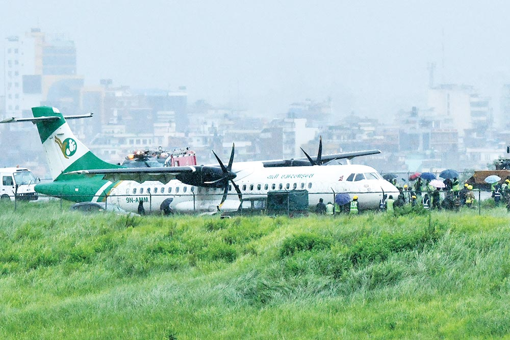 Nepali army along with emergeny and airport personnel are seen next to a Yeti Airlines aircraft after it skidded off the runaway during landing at the Tribhuvan International Airport in Kathmandu on Friday.photo : AFP