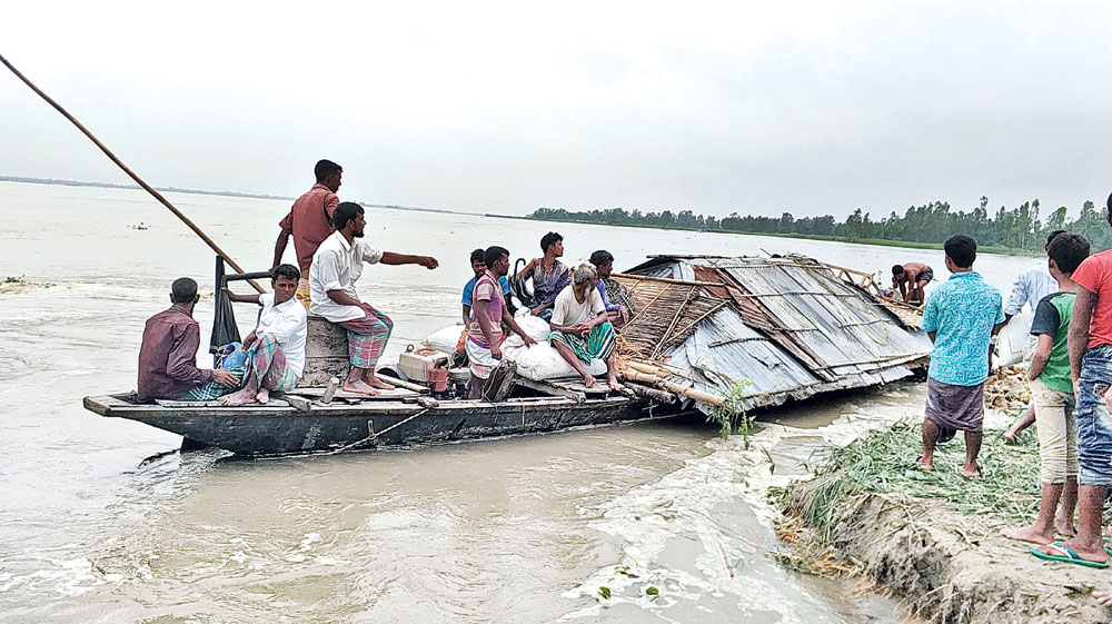 A flood affected family moving their house by boat to a safe place. The photo was taken from Kutipara under Mohiskocha union of Aditmari upazila in Lalmonirhat on Monday.