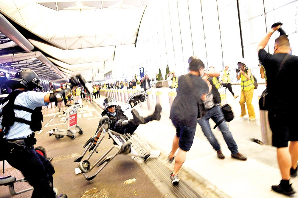 "Police scuffle with pro-democracy protesters at Hong Kong's international airport on August 13. Hundreds of flights were cancelled or suspended at Hong Kong's airport on August 13 as pro-democracy protesters staged a second disruptive sit-in at the sprawling complex, defying warnings from the city's leader who said they were heading down a ""path of no return"".	photo : AFP"