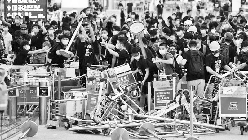 Pro-democracy protestors block the entrance to the terminals at Hong Kong's international airport on August 13, 2019.