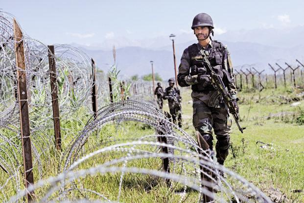 An Indian Army soldier patrols on the fence near the India-Pakistan LoC in Poonch. Photo: Hindustan Times
