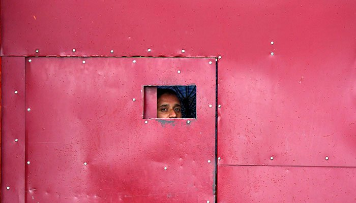 A worker looks through the gate of a closed school in Srinagar on August 19, 2019. Photo: AFP