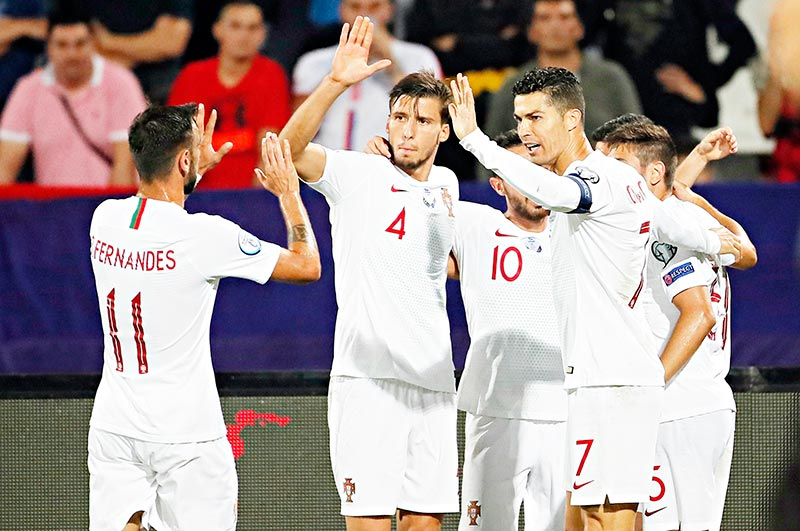(FromL) Portugal's midfielder Bruno Fernandes, Portugal's defender Ruben Dias  and Portugal's forward Cristiano Ronaldo celebrate a goal during the EURO 2020 football qualification match between Serbia and Portugal in Belgrade, Serbia, on September 7, 2019.photo: AFP
