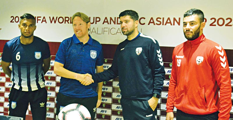 Coaches of Bangladesh (L) and Afghanistan (R) shaking hands in presence of team skippers at a pre-match briefing on Monday before their meet in the Second Round of the Preliminary Joint Qualification of FIFA World Cup 2022 and AFC Asian Cup 2023.	photo: BFF