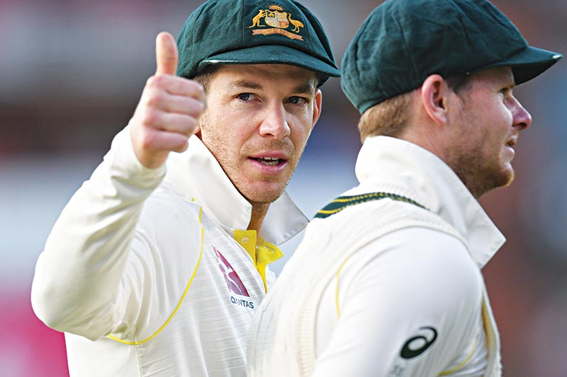 Australia's captain Tim Paine (L) gestures beside Australia's Steve Smith as his players celebrate their victory on the field after the fourth Ashes cricket Test match between England and Australia at Old Trafford in Manchester, north-west England on September 8, 2019. - Australia retained the Ashes with a 185-run thrashing of England in the fourth Test at Old Trafford on Sunday. 	photo: AFP